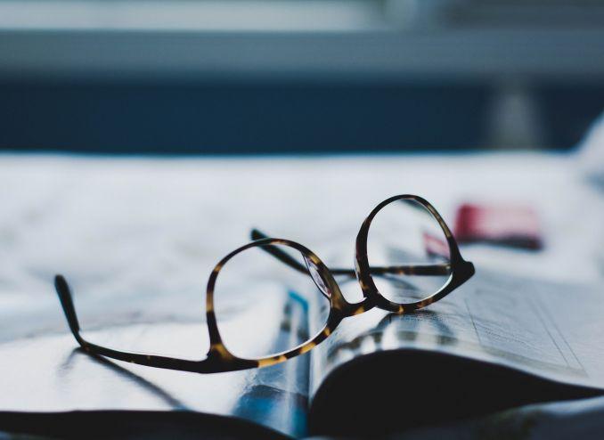 occhiali su una rivista di esercizi di tedesco
